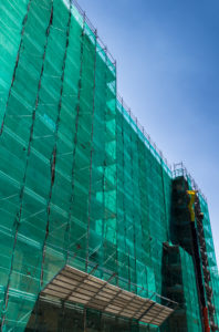 Modern building is under construction, metal scaffolding with green network cover agaist blue sky.